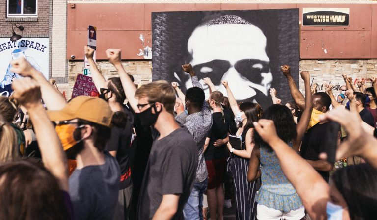 A group of people raise their fist in front of a mural of George Floyd